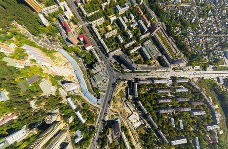 aerial: Vista a la ciudad aérea con el cruce de caminos y carreteras, casas, edificios, parques y estacionamientos, puentes. Tiro helicóptero. Imagen panorámica. Foto de archivo