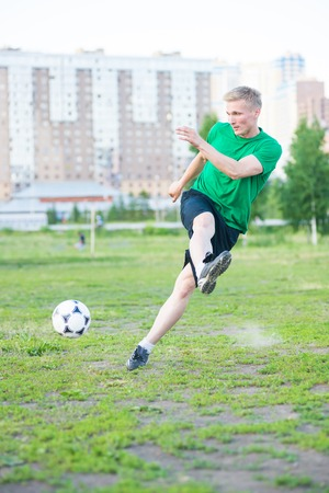 strongly: Soccer player strongly hits the ball. City park playground.