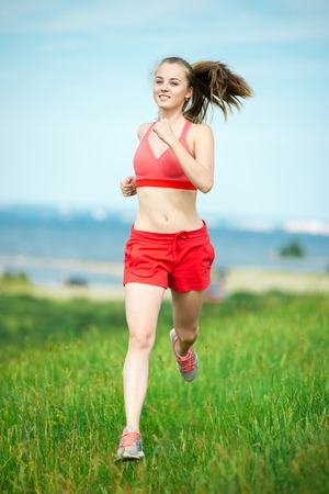 relaxation exercise: Young lady running. Woman runner running through the summer park rural road. Workout in a park. Beautiful fit girl. Fitness model caucasian ethnicity outdoors. Weight loss exercise. Jogging.