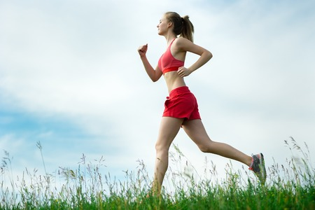 lady: Young lady running. Woman runner running through the summer park rural road. Workout in a park. Beautiful fit girl. Fitness model caucasian ethnicity outdoors. Weight loss exercise. Jogging.