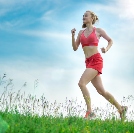 caucasian ethnicity: Young lady running. Woman runner running through the summer park rural road. Workout in a park. Beautiful fit girl. Fitness model caucasian ethnicity outdoors. Weight loss exercise. Jogging.