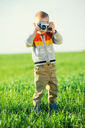 film shooting: Little boy with an old camera shooting outdoor. Kid taking a photo using a vintage retro film cam. Green summer field.
