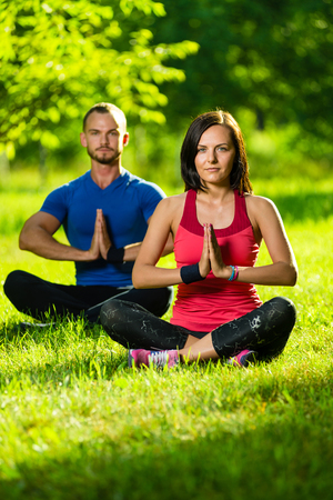 meditating woman: Young man and woman doing yoga in the sunny summer park. Couples Yoga on green grass outdoor.