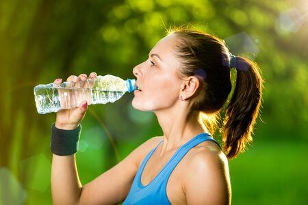 mujeres fitness: Joven mujer de agua potable despu�s del ejercicio f�sico. Bebida fr�a en verano, parque verde. Deporte al aire libre