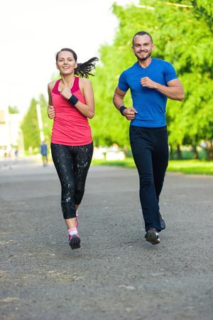 adentro y afuera: Los corredores de entrenamiento al aire libre ejercicio. Ciudad pareja que lleva a correr afuera. Entrenamiento deportivo de la ciudad en el parque verde. Foto de archivo