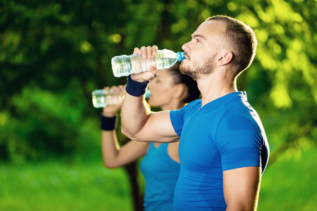 standing water: Man and woman drinking water from bottle after fitness sport exercise. Smiling couple with bottles of cold drink outdoors