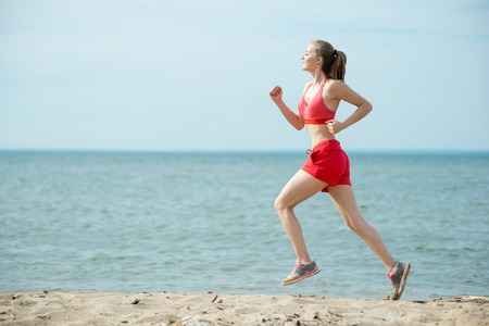 running: Young lady running. Woman runner running at the sunny summer sand beach. Workout near ocean sea coast. Beautiful fit girl. Fitness model caucasian ethnicity outdoors. Weight loss exercise. Jogging.