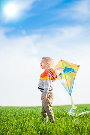 kite: Young boy flies his kite in an open field. Little kid playing with kite on green meadow. Childhood concept. Stock Photo