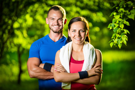 sports clothing: Athletic man and woman after fitness exercise. Beautiful young couple in sports clothing after outdoor exercises. White towel. Stock Photo
