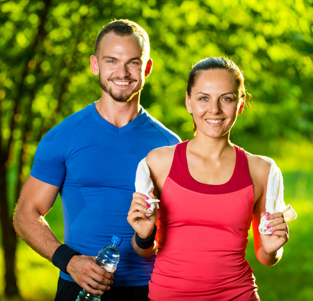 outdoor exercise: Athletic man and woman after fitness exercise. Beautiful young couple in sports clothing after outdoor exercises. White towel. Stock Photo