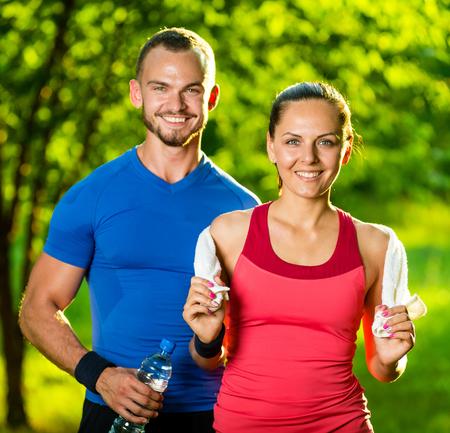 ejercicio: Atl�tico hombre y la mujer despu�s del ejercicio f�sico. Hermosa joven pareja en ropa deportiva despu�s de los ejercicios al aire libre. Toalla blanca.