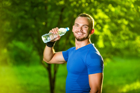 man drinking water: Athletic sport man drinking water from a bottle. Cold drink after outdoor fitness.