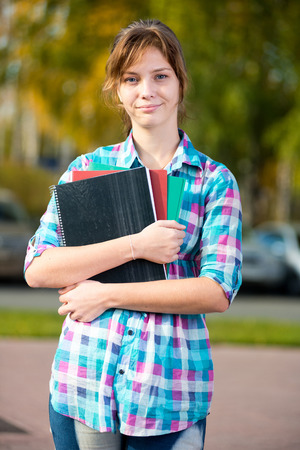 autodidact: Portrait of young alluring woman holding education books. Standing at summer college park. Student girl.