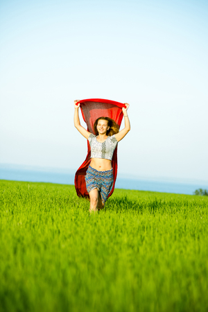 caucasian ethnicity: Young lady runing with tissue in green field. Beautiful happy woman walking in the summer rural meadow. Beautiful fit tan girl. Sexy slim model caucasian ethnicity outdoors.