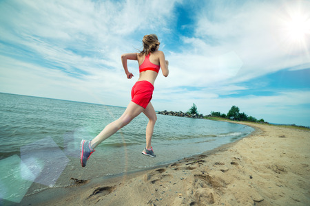 jogging: Young lady running. Woman runner running at the sunny summer sand beach. Workout near ocean sea coast. Beautiful fit girl. Fitness model caucasian ethnicity outdoors. Weight loss exercise. Jogging.