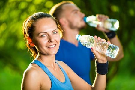 tomando agua: El hombre y la mujer bebiendo agua de botella despu�s del ejercicio de fitness deporte. Sonriente pareja con botellas de bebida fr�a al aire libre Foto de archivo