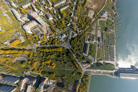 water power: Aerial water power plant view with crossroads and roads, houses, buildings, parks and parking lots, bridges. Copter shot. Panoramic image. Stock Photo