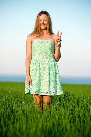 vitality: Happy playfull vitality freedom girl stands in green field. Woman lifestyle