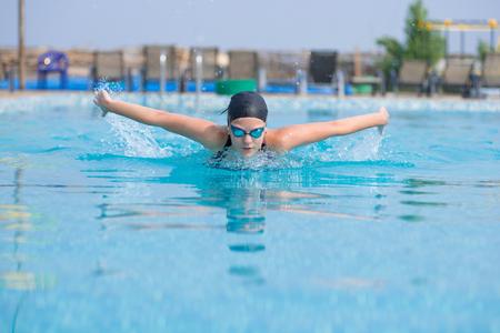 Ragazza in occhiali di protezione e protezione di nuoto farfalla stile del tratto in piscina di acqua blu