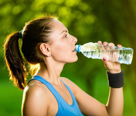 water sport: Young woman drinking water after fitness exercise. Cold drink  at summer green park. Outdoor sport Stock Photo