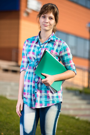 Portrait of young alluring woman holding education books. Standing at summer college park. Student girl.