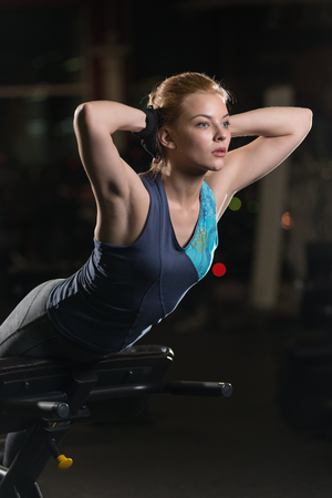 laying abs exercise: Woman doing strength exercises for abdominal muscles at indoor sport gym. Girl doing yoga stretches after running. Fitness model in dark sport club.
