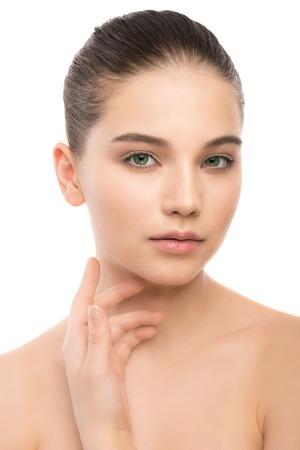 Portrait de la belle jeune femme brune avec un visage propre. Beauté modèle de spa fille avec la peau fraîche et propre parfait. En regardant la caméra et souriant. Jeunesse et le concept de soins de la peau. Isolé sur un fond blanc.