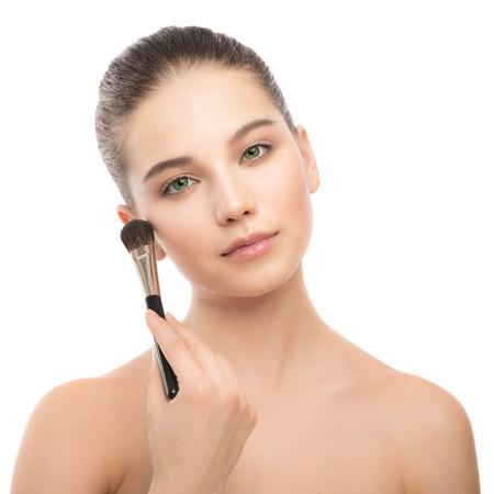 Ritratto di giovane e bella donna bruna con faccia pulita. Modello di bellezza spa ragazza con perfetta pelle pulita fresca applicando pennello cosmetico. Gioventù e il concetto di cura della pelle. Isolato su uno sfondo bianco.