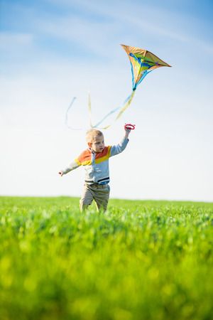 Young boy flies his kite in an open field. Little kid playing with kite on green meadow. Childhood concept. Stock Photo