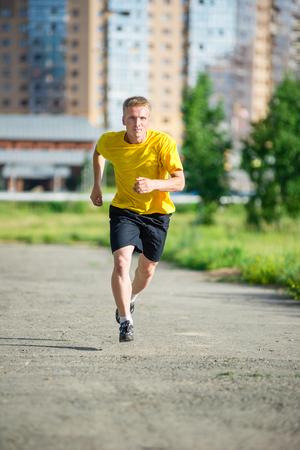 caucasian ethnicity: Running man jogging in city street park at beautiful summer day. Sport fitness model caucasian ethnicity training outdoor. Stock Photo