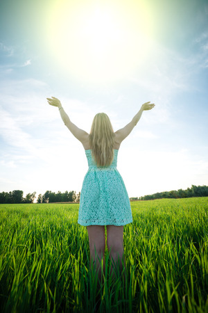 Happiness woman stay outdoor under sunlight of sunset. With raised hands at the sunrise time