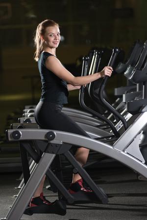 Mujer jovén ejercitando en el gimnasio. Ejecutar en una máquina. El activar sesión de ejercicios en el gimnasio oscuro. Cardio.