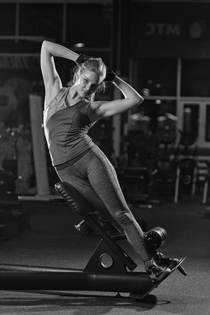 laying abs exercise: Woman doing strength exercises for abdominal muscles at indoor sport gym. Girl doing yoga stretches after running. Fitness model in dark sport club. Black and white.