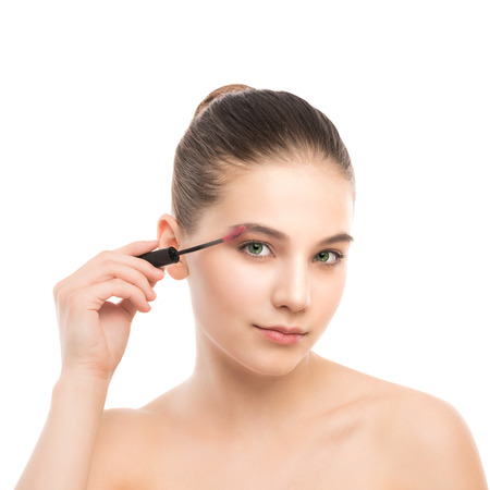 smoky black: Eye make up apply. Mascara applying closeup, long lashes. Mascara brush. Portrait of beautiful young brunette woman with perfect fresh clean face skin. Eyelashes extensions. Make-up for green eyes. Isolated on a white background.