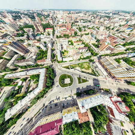 popular: Aerial city view with crossroads and roads, houses, buildings, parks and parking lots. Sunny summer panoramic image Stock Photo