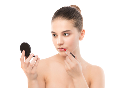 Young brunette woman with perfect clean face applying lipstick using mirror. Isolated on a white. Stock Photo