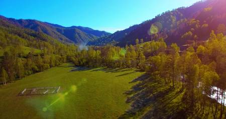 daybreak: Mid air flight over fresh mountain river and meadow at sunny summer morning. Rural dirt road below.