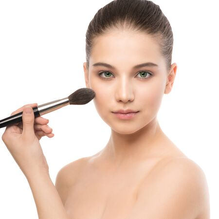 beautify: Young brunette woman with clean face. Girl perfect skin applying cosmetic brush. Isolated on a white. Stock Photo