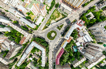 air traffic: Aerial city view with crossroads and roads, houses, buildings, parks and parking lots. Sunny summer panoramic image Stock Photo