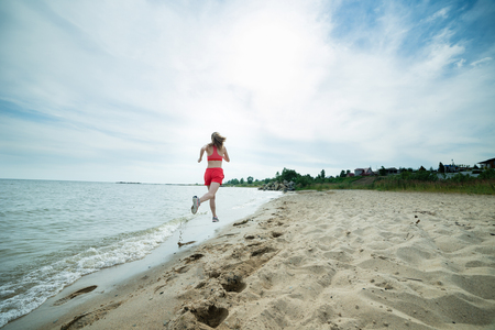 Young lady running at the sunny summer sand beach. Workout.  Jog photo