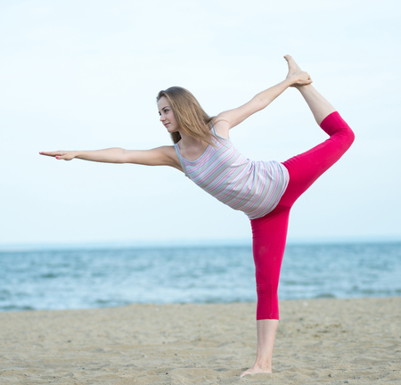 Young lady practicing yoga. Workout near ocean sea coast. photo