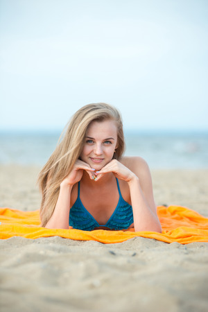 Young lady sunbathing on a beach. Beautiful woman posing at the photo
