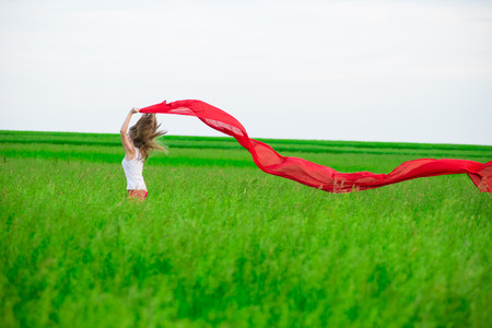 Young lady runing with tissue in green field. Woman with scarf. photo