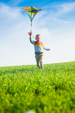 Young boy playing with his kite in a green field. photo