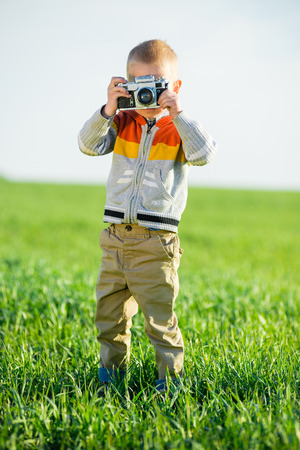Little boy with an old camera shooting outdoor. photo