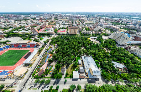 Aerial city view with crossroads and roads, houses, buildings, parks and parking lots, bridges. Helicopter drone shot. Wide Panoramic image. Stock Photo