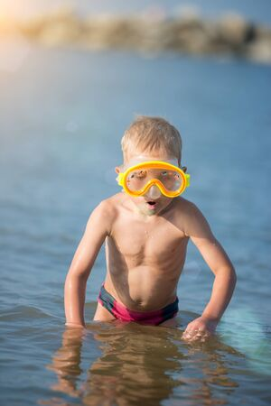 Cute little kid wearing mask and flippers for diving at sand tropical beach. photo
