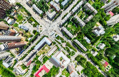 Aerial city view with crossroads and roads, houses, buildings, parks and parking lots. Sunny summer panoramic image Reklamní fotografie