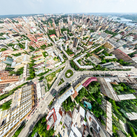 Aerial city view with crossroads and roads, houses, buildings, parks and parking lots. Sunny summer panoramic image Stock Photo