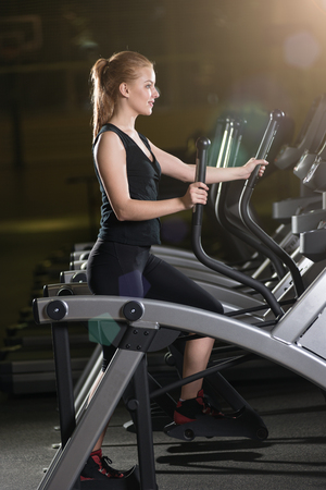 Young woman at the gym exercising. Run on machine. Standard-Bild